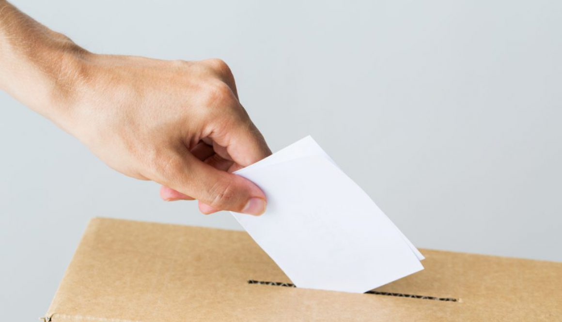 man putting his vote into ballot box on election