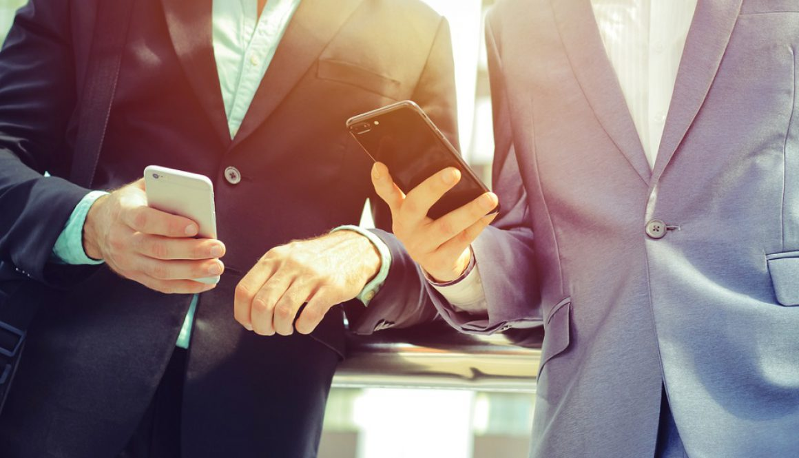 Midsection of two colleague businessmen using smartphone at the