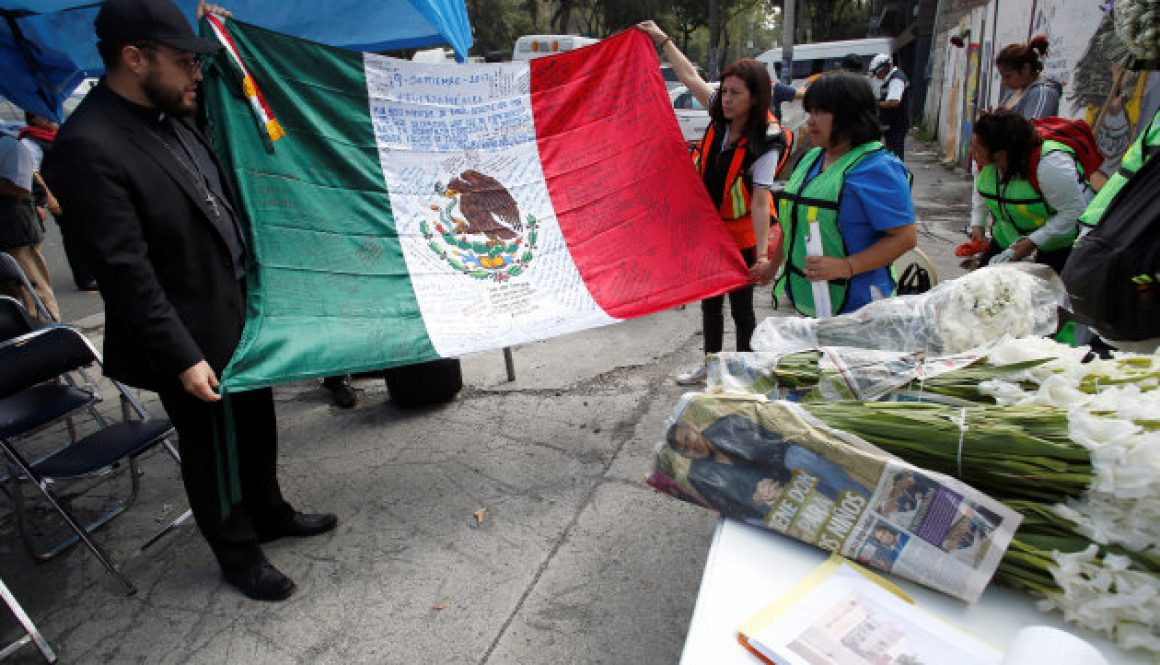 People spread a Mexican flag before homage to victims of building collapse during September 2017 earthquake in Mexico City